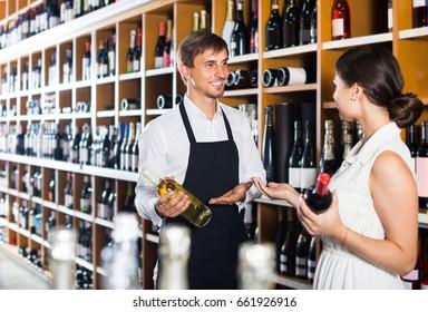 portrait of positive american male seller in uniform showing bottle of wine to female customer in wine shop