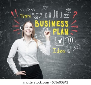 Portrait of a positive blond woman standing near a blackboard with a colorful business plan drawing on it.
