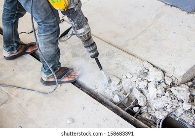 Portrait of positive Builder worker with pneumatic hammer drill equipment at construction site