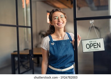 Portrait of positive business woman standing at cafeteria door entrance. Cheerful young waitress in blue apron near glass door with open signboard and looking at camera. Excited small business owner.