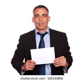 Portrait of a positive businessman looking happy and holding a white card with copyspace on isolated background