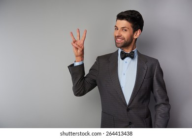 Portrait of positive casual young man wearing tweed jacket and bow tie. Man smiling, showing three fingers and looking at camera