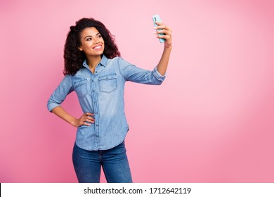 Portrait of positive cheerful afro american girl make selfie on spring time travel journey wear casual style clothes isolated over pink color background