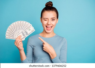 Portrait positive cheerful content student top-knot beautiful hold hand banknotes millionaire cash fun funky advise ads choice decision present casino trendy stylish sweater isolated blue background