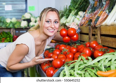 Portrait of positive cheerful glad woman buying organic tomatoes in shop