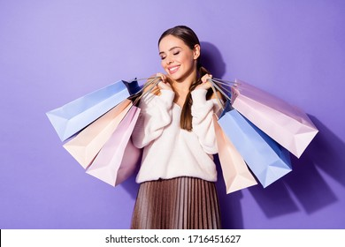 Portrait of positive cheerful lovely girl addicted shopaholic enjoy 50 sales hold many purchase bags wear good look clothes isolated over violet color background
