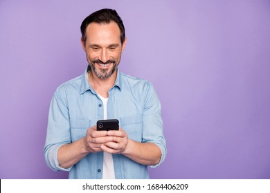 Portrait of positive cheerful man use smart phone chatting blog post follow bloggers share social media information wear good looking clothing isolated over violet color background