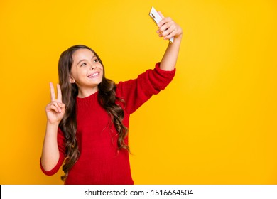 Portrait of positive cheerful wavy hair model kid have fun on leisure trip take selfie make v-sign video call wear stylish trendy pullover isolated over yellow bright color background