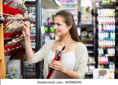 Portrait of positive cheerful woman choosing brushes for drawing in art shop