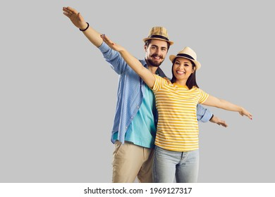 Portrait of positive cheerful young caucasian couple tourist wearing summer hat posing with arms like airplane wings looking at camera. Travel and vacation concept. Shot with studio background