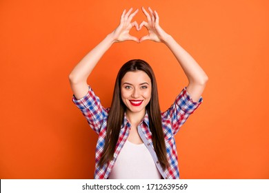 Portrait of positive cute lovely sweet girl show heart shape finger symbol enjoy boyfriend love date wear checkered clothes isolated over shine color background