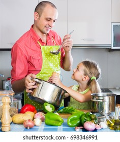 Portrait of positive dad and little daughter cooking at home