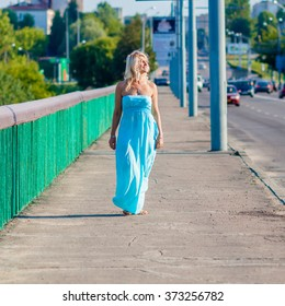 Portrait of positive elderly blonde woman on the bridge. Mature beautiful blonde in blue dress walks on the bridge. the concept of transition to old age