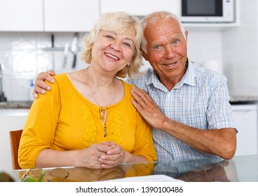 Portrait of positive elderly family couple sitting at kitchen table