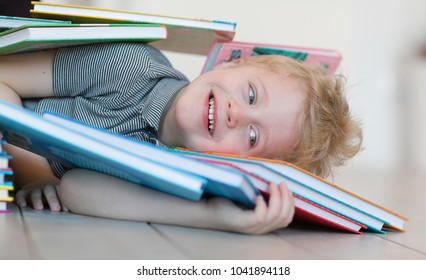 Portrait of positive and emotional little boy with blond hair lying with a smile on his face on the wooden floor in the playroom in an embrace with books after a reading lesson at a children's center