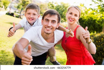 Portrait of  positive family with boy sitting on father's back hugging each other in park