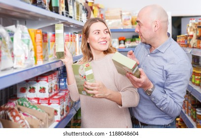 Portrait of  positive family couple  customers choosing groats in  grocery food shop