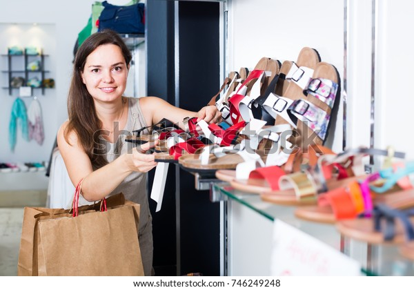 Portrait of positive female customer selecting shoes in footgear center