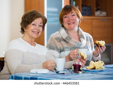 Portrait of positive female pensioners drinking tea and laughing