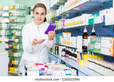 Portrait of positive female pharmacist is sshowing medicines in pharmacy