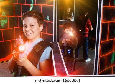 Portrait of positive friendly smiling preteen boy with laser pistol posing in laser tag labyrinth
