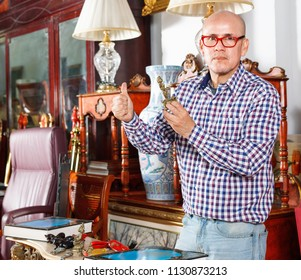 Portrait of  positive friendly  successful owner of antiques shop among vintage things