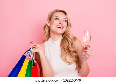Portrait of positive funky girlfriend, elegant laughing chick having colorful packets with presents gifts, beverage in hands isolated on pink background