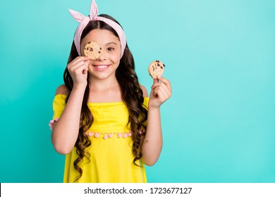 Portrait of positive girl child close cover eyes face chocolate cookies snack wear retro stylish trendy yellow shirt dress isolated over teal color background