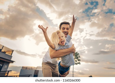 Portrait of positive girl flourishing hands while playing with outgoing unshaven father under sky with clouds