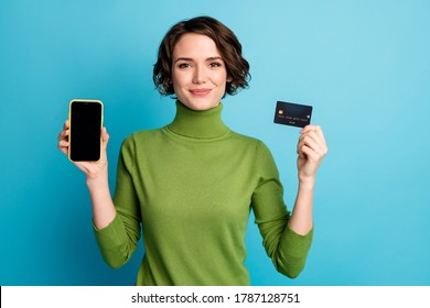 Portrait of positive girl hold smartphone credit card enjoy online banking paying modern technology wear green style stylish trendy jumper isolated blue color background