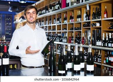 portrait of positive  glad male customer taking bottle of wine in store