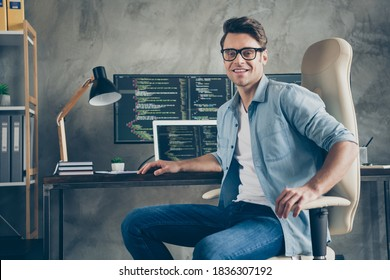 Portrait of positive guy it specialist sit chair desk enjoy working pc home ready debugging java script cyber space error wear denim jeans shirt in workplace