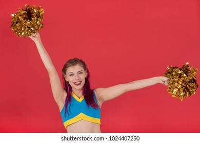 Portrait of a positive and happy beautiful young cheerleader girl in a blue suit with Pom poms in her hands looking with a smile at the camera on a red wall background. Cheerleading team.
