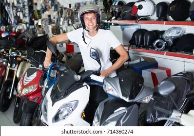 Portrait of positive italian glad male in helmet on motorbike in the store