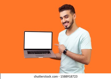 Portrait of positive joyful brunette man with beard in white t-shirt standing holding laptop with blank screen and smiling at camera, internet advertising. studio shot isolated on orange background