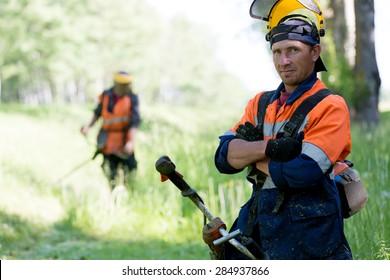 Portrait positive landscaper man worker with gas handheld string trimmer equipment during grass cutting team works