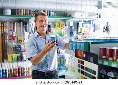 Portrait of  positive male customer selecting paint can in housewares department