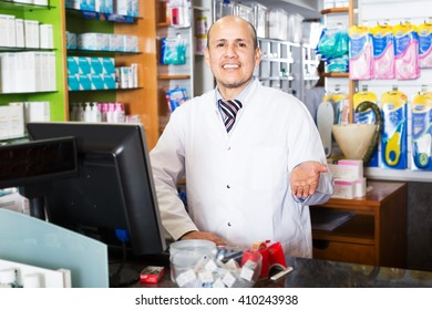 Portrait of positive male pharmacist working in modern farmacy and smiling