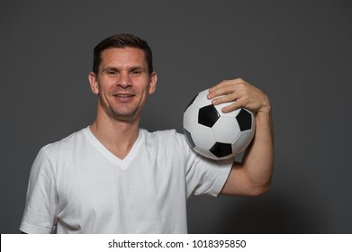 Portrait of a positive male soccer or football player or fan with ball on gray background