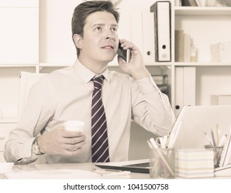 Portrait of positive male working in office and talking on mobile phone