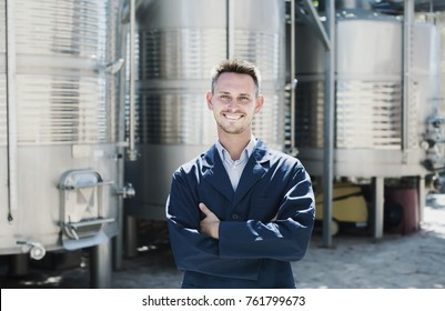 Portrait of positive man winery worker standing on wine factory in secondary fermentation section