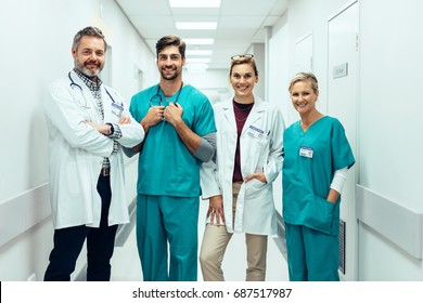 Portrait of positive medical professionals standing in hallway and looking at camera. Group of paramedics smiling in hospital corridor.