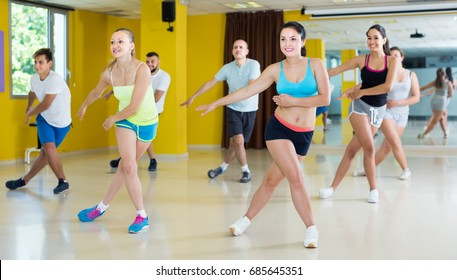 Portrait of positive men and women dancing zumba in dance class