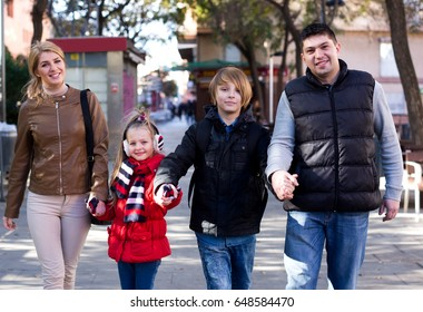 Portrait positive parents with children posing outdoor in cold day and smiling