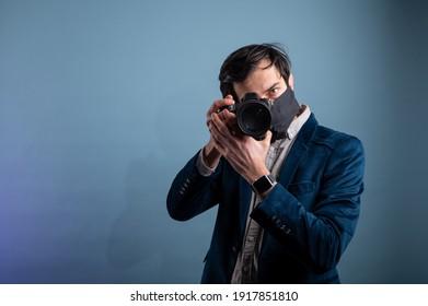 Portrait of positive photographer, man with medical mask holding professional digital dslr camera. Indoor studio shot isolated on blue background.The photographer is wearing a medical mask.