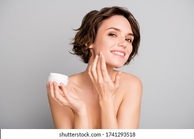 Portrait of positive pretty girl prepare dating look in mirror apply new skin care cream on her face to make face soft fresh nature isolated over grey color background - Shutterstock ID 1741293518