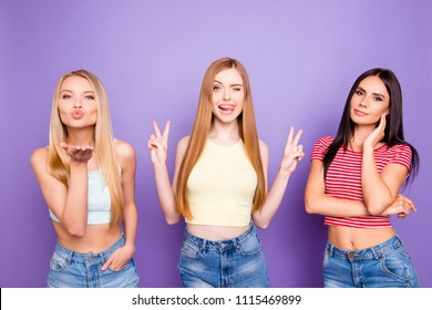 Portrait of positive pretty girls making different actions sending air kiss with palm gesturing v-signs and tongue out winking with eye posing over vivid violet background
