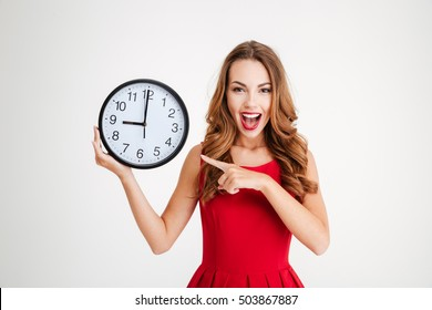 Portrait of positive pretty young woman in red santa claus dress pointing at wall clock over white background