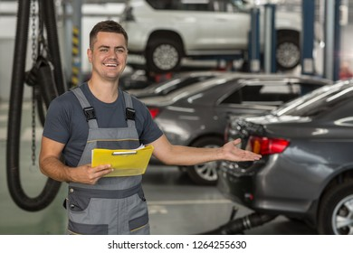 Portrait of positive repairman in uniform showing with hand auto service equipped with modern technology. Smiling mechanic keeping folder, gesturing with hand on cars and looking at camera.