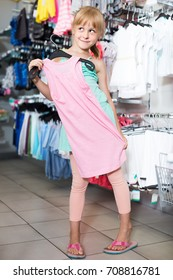 Portrait of positive russian girl choosing colored dress and wear in the shop